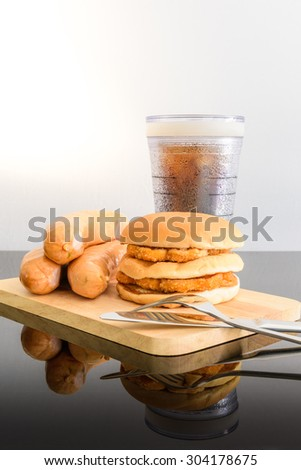 pork sausage, chicken hamburger and glass of cola on wooden cutting board with Knife and fork on top table, reflections