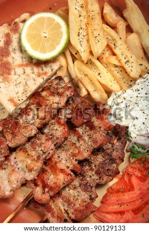 pork skewers served on a plate with fries tzatziki pita and tomato in a greek style - stock photo