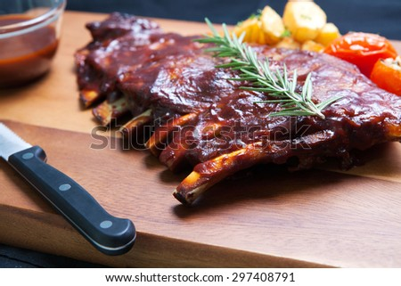 Pork Spareribs with tomato and fried potatoes on wooden plate served with BBQ sauce - stock photo