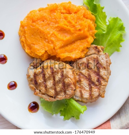 Pork steak fried on a grill with mashed sweet potatoes, lunch in restaurant, beautiful presentation