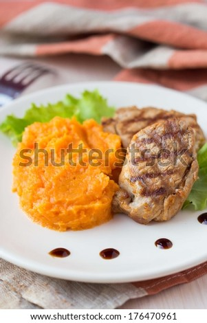 Pork steak fried on a grill with mashed sweet potatoes, lunch in restaurant, beautiful presentation - stock photo
