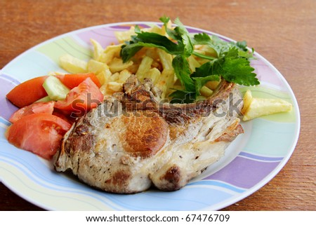 pork steak ,fried potatoes with  salad - stock photo