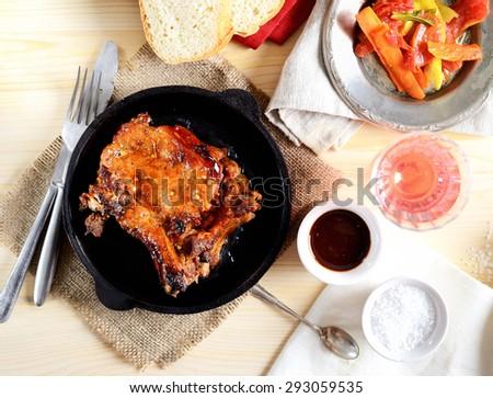 pork steak in a frying pan, fried vegetables - stock photo