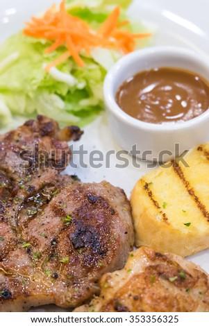 Pork steak , salad and garlic bread on a white plate - stock photo