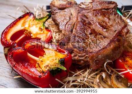 Pork steak with grilled peppers, tomatoes and mushrooms on the grill , with Tabasco sauce on plate with the decor in the form of hay and with a knife for steaks