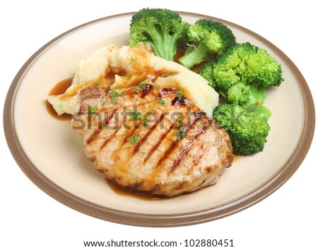 Pork steak with mashed potato, broccoli and gravy. - stock photo
