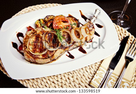 Pork steak with onion, tomatos and rosemary on white plate - stock photo