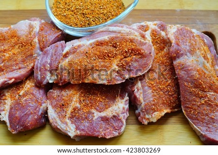 pork steak with spices - products on the grill,