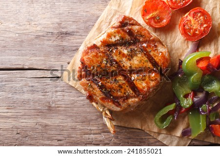 pork steak with vegetables close-up on paper, horizontal top view, rustic style  - stock photo