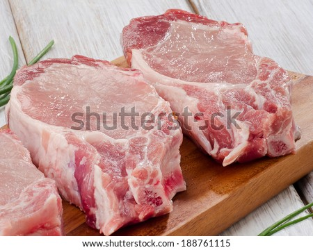 pork steaks on a wooden board. Selective focus