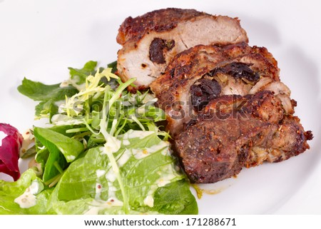 Pork stuffed with prunes and salad - stock photo