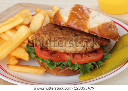 Pork tenderloin, lettuce and tomatoes on a bun with french fries