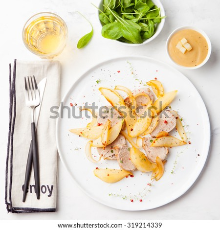 Pork tenderloin roasted with pear and onion on a white plate with glass of white wine, and fresh spinach salad on a white background
