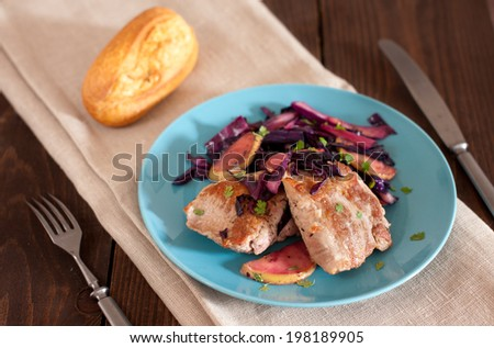 pork tenderloin with apples, cabbage and baguette - stock photo
