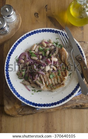 Pork with agrodolce sauce and white beans - stock photo