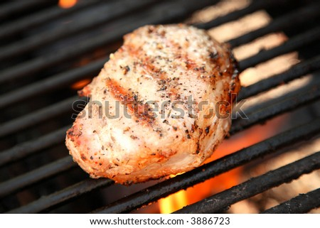 Porkchop on the grill with flame in background