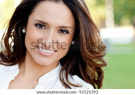 Porrait of a beautiful woman smiling outdoors - stock photo