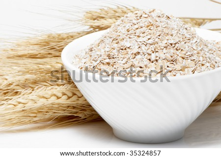 Porridge and Wheat ears on a white background - stock photo