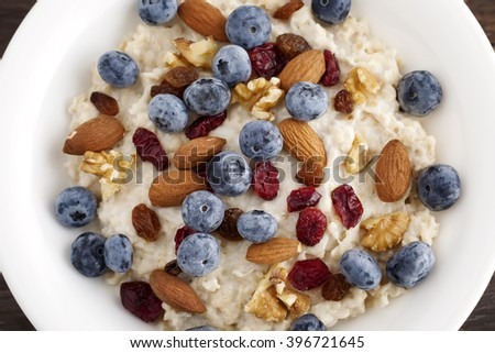 Porridge breakfast with blueberry, dried cranberries, almonds and walnuts. - stock photo