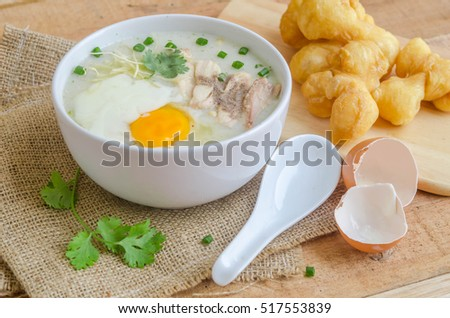 Porridge, chicken Porridge (congee) and Soft-boiled egg served in white bowl with deep-fried doughstick