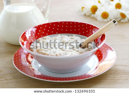 Porridge for breakfast in a red bowl on wooden table - stock photo