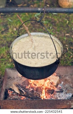 Porridge in a pot on the fire - stock photo