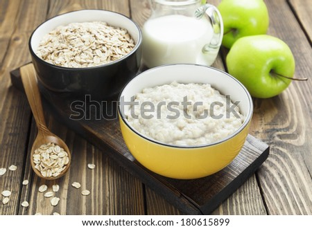 Porridge, oats, milk and green apples on the table - stock photo