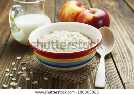 Porridge, oats, milk and red apples on the table - stock photo