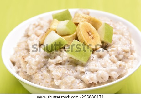 Porridge oats with apple and bananas slices, close up view - stock photo