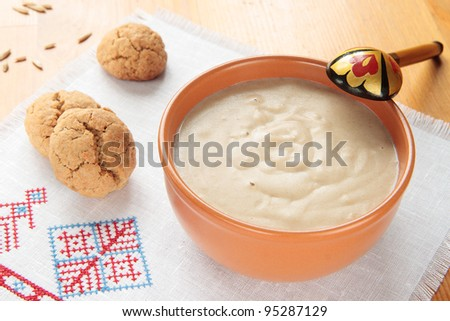 Porridge of oatmeal in a ceramic bowl and oat cookies - stock photo