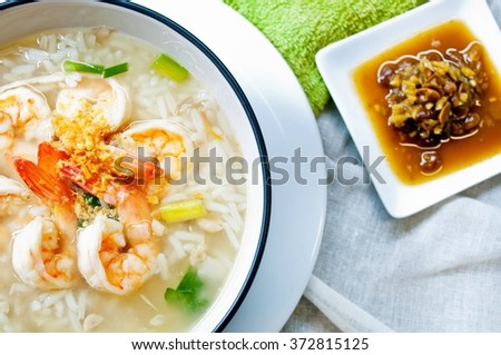 Porridge rice with shrimps and fried garlic. On fabric background. With sauce made from salted soybean mix with chili on white background. Shallow depth of field. - stock photo