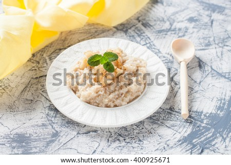 porridge with apples in a plate on a table, selective focus