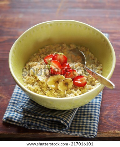 Porridge with banana and strawberry in a bowl for healthy breakfast, selective focus