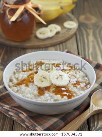 Porridge with bananas and honey in a bowl on the table