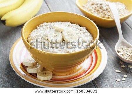 Porridge with bananas in a yellow bowl on the table - stock photo