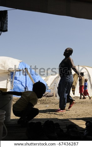 PORT-AU-PRINCE - AUGUST 28:  A contrasty image of a  woman carrying water  for her daily needs while a kid enjoying himself  in one of the tent cities, in Port-Au-Prince, Haiti on August 28, 2010. - stock photo