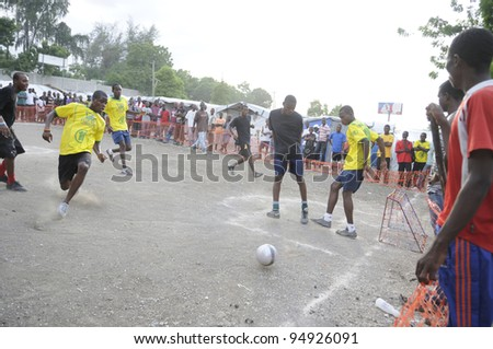 PORT-AU-PRINCE - AUGUST 26: A football player tries to score a goal during a friendly soccer match in Port-Au-Prince, Haiti on August 26, 2010. - stock photo