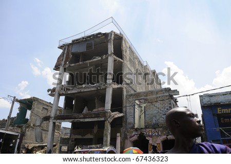PORT-AU-PRINCE - AUGUST 27: A Haitian traveling on a tap-tap in the downtown of the capital where most of the affected buildings still remain in a risky , in Port-Au-Prince, Haiti on August 27, 2010. - stock photo