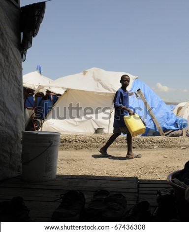 PORT-AU-PRINCE - AUGUST 28: A Haitian unidentified kid going pass a tent to collect water for his family for a day , in Port-Au-Prince, Haiti on August 28, 2010. - stock photo