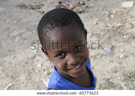"""PORT-AU-PRINCE - AUGUST 28:  A small unidentified kid during his leisure time  in the Tent city called """" ACRA""""on August 28, 2010 in Port-Au-Prince, Haiti - stock photo"""