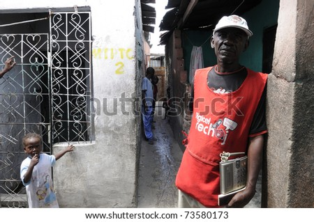 PORT-AU-PRINCE - AUGUST 25: A vendor standing with a wireless phone to provide residents  a chance to call their loved ones after the earthquake in Cite Soleil,in Port-Au-Prince,Haiti on August 25,2010 - stock photo