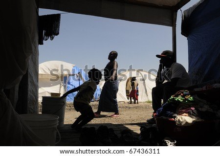PORT-AU-PRINCE - AUGUST 28:  A woman carrying water for her daily needs as seen from inside a tent, in Port-Au-Prince, Haiti on August 28, 2010. - stock photo