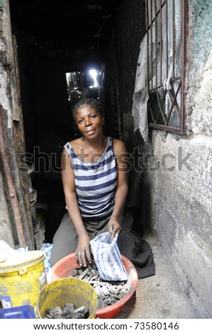 PORT-AU-PRINCE - AUGUST 25: A woman selling coal in her shack after the earthquake destroyed her house just to survive in Cite Soleil, in Port-Au-Prince, Haiti on August 25, 2010. - stock photo