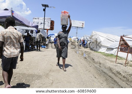 PORT-AU-PRINCE - AUGUST 28:  A woman selling  cold drinks during  hot and humid afternoon in one of the tent cities  in  Port-Au-Prince, Haiti on August 28, 2010. - stock photo