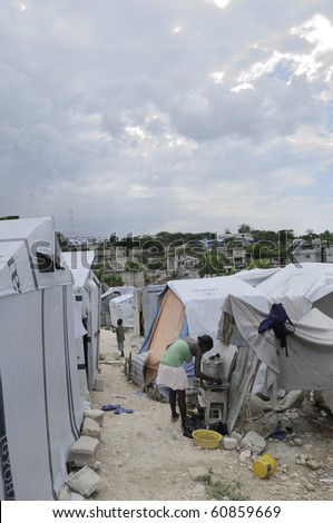 PORT-AU-PRINCE - AUGUST 28:   A young girl cooking outside her tent in on of the tent cities  in Port-Au-Prince, Haiti on August 28, 2010. - stock photo