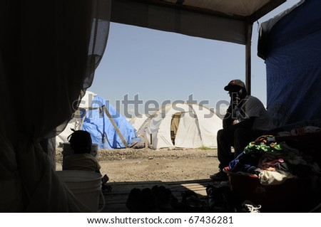 PORT-AU-PRINCE -AUGUST 28: A young Haitian adult sitting in front of his tent, most of the young Haitians has nothing to do except passing their time,  in Port-Au-Prince, Haiti on August 28,2010. - stock photo