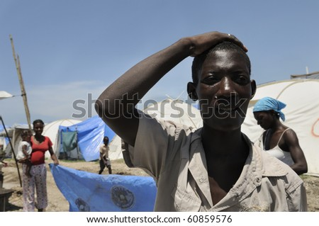 PORT-AU-PRINCE - AUGUST 28:  A young man who sells ice cubes in the tent cities explaining his situation in one of the tent cities  in  Port-Au-Prince, Haiti on August 28, 2010. - stock photo