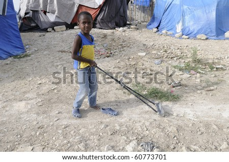 PORT-AU-PRINCE - AUGUST 28:  A young unidentified kid playing  beside his tent on August 28, 2010 in Port-Au-Prince, Haiti. - stock photo