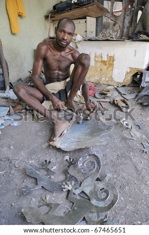 PORT-AU-PRINCE - AUGUST 25: An artist from Cite Soleil-on of the  most dangerous  area  in the world making iron mementos in his workplace,  in Port-Au-Prince, Haiti on August 25, 2010.