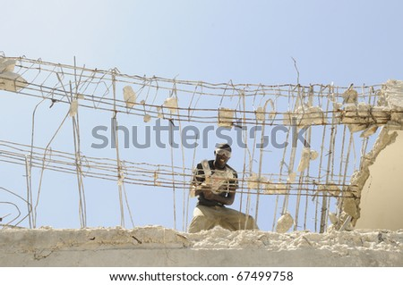 PORT-AU-PRINCE - AUGUST 30:  An Haitian worker using a sledge hammer to break down the  skeleton of a building  in Port-Au-Prince, Haiti on August 30, 2010. - stock photo